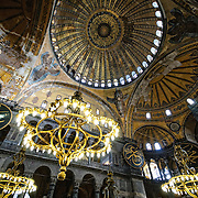 The lights and ornate dome ceiling of Hagia Sophia in Istanbul, Turkey. Originally built as a Christian cathedral, then converted to a Muslim mosque in the 15th century, and now a museum (since 1935), the Hagia Sophia is one of the oldest and grandest buildings in Istanbul. For a thousand years, it was the largest cathedral in the world and is regarded as the crowning achievement of Byzantine architecture.