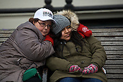 Toronto, Canada residents Jennifer Kay, 47, left, and her niece Cailey Bonikowsky, 22, to a prayer over the loud speaker as they sit outside of the parade route along Pennsylvania Ave. during the inauguration ceremony on January 21, 2013 in Washington, D.C.
