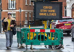 © Licensed to London News Pictures. 27/12/2020. London, UK. Members of the public walk past a Covid-19 information display in Fulham, South West London as Ministers reveal that the Oxford vaccine could be approved next week and possibly as early as Monday (tomorrow) with a full roll out to start from the 4 January 2021. Last week Health Secretary Matt Hancock announced that yet another new Covid-19 mutation has been discovered in the UK as Downing Street orders many more areas of England to go into Tier 4 lockdown yesterday with tougher new Covid-19 restrictions for many as the mutated strains continue to spread throughout the UK. Photo credit: Alex Lentati/LNP