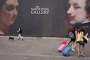 Three young women pull their baggage on wheels, past the large portraits publicising an Arts event at London's national Gallery.