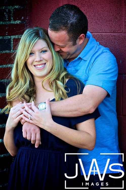 Wedding engagement picture taken in Deep Ellum of groom hugging his bride and whispering in her ear.