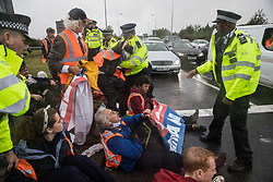 Colnbrook, UK. 27th September, 2021. Metropolitan Police officers remove Insulate Britain climate activists from a slip road from the M25 at Junction 14 close to Heathrow airport which they had blocked as part of a campaign intended to push the UK government to make significant legislative change to start lowering emissions. The activists are demanding that the government immediately promises both to fully fund and ensure the insulation of all social housing in Britain by 2025 and to produce within four months a legally binding national plan to fully fund and ensure the full low-energy and low-carbon whole-house retrofit, with no externalised costs, of all homes in Britain by 2030.