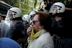 October 3, 2016 - Athens, Greece - A pensioner woman uses her scarf after tear gas usage from the riot police in Athens, on Monday October 3, 2016. Greek pensioners taking part at a protest march against pension cuts, demanted meeting with Prime minister but were stoped with tear gas by riot police close to the government's headquarters. (Credit Image: © Panayiotis Tzamaros/NurPhoto via ZUMA Press)