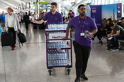 Heathrow staff hand out free bottles of water to stranded passengers at Terminal 5 at Heathrow Airport after an IT glitch brings British Airways systems to a halt, causing disruption to thousands of passengers with flights cancelled and delayed. London, August 07 2019.