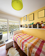 Boy's bedroom with a shelf full of toys. Window overlooking the garden