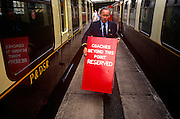 A volunteer heritage railway enthusiast adjusts a platform sign at the Paignton steam museum.
