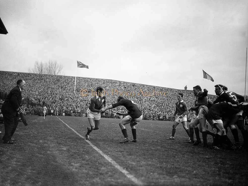Irish back, W R Hunter, on the left, in possession on the sideline, about to be tackled by Scottish forward, N S Bruce,.. Irish Rugby Football Union, Ireland v Scotland, Five Nations, Landsdowne Road, Dublin, Ireland, Saturday 24th February, 1962,.24.2.1962, 2.24.1962,..Referee- N M Parkes, Rugby Football Union, ..Score- Ireland 6 - 20 Scotland, ..Irish Team, ..F G Gilpin, Wearing number 15 Irish jersey, Full Back, Queens University Rugby Football Club, Belfast, Northern Ireland,..W R Hunter, Wearing number 14 Irish jersey, Right Wing, C I Y M S Rugby Football Club, Belfast, Northern Ireland, ..M K Flynn, Wearing number 13 Irish jersey, Right Centre, Wanderers Rugby Football Club, Dublin, Ireland, ..D Hewitt, Wearing number 12 Irish jersey, Left centre, Instonians Rugby Football Club, Belfast, Northern Ireland,..N H Brophy, Wearing number 11 Irish jersey, Left wing, Blackrock College Rugby Football Club, Dublin, Ireland, ..G G Hardy, Wearing  Number 10 Irish jersey, Stand Off, Bective Rangers Rugby Football Club, Dublin, Ireland,  ..J T M Quirke, Wearing number 9 Irish jersey, Scrum Centre, Blackrock College Rugby Football Club, Dublin, Ireland, ..S Millar, Wearing number 1 Irish jersey, Forward, Ballymena Rugby Football Club, Antrim, Northern Ireland,..A R Dawson, Wearing number 2 Irish jersey, Forward, Wanderers Rugby Football Club, Dublin, Ireland, ..R J McLoughlin, Wearing number 3 Irish jersey, Forward, University College Dublin Rugby Football Club, Dublin, Ireland, ..W A Mulcahy, Wearing number 4 Irish jersey, Captain of the Irish team, Forward, Bohemians Rugby Football Club, Limerick, Ireland,..W J McBride, Wearing number 5 Irish jersey, Forward, Ballymena Rugby Football Club, Antrim, Northern Ireland,..D Scott, Wearing number 6 Irish jersey, Forward, Malone Rugby Football Club, Belfast, Northern Ireland, ..M L Hipwell, Wearing number 8 Irish jersey, Forward, Terenure Rugby Football Club, Dublin, Ireland, ..M G Culliton, Wearing number 7 Irish jersey, Forward
