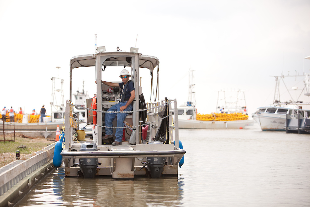 A cleanup worker waits as a storm nears the Co Co Marina in Cocodrie, LA.