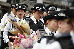 © Licensed to London News Pictures. 07/06/2017. London, UK. First responder police officers who were on duty during the Saturday night's terror attack visit the scene on London Bridge for the first time since the attack and leave flowers for the victims of the attack, which killed 8 people on London Bridge and at Borough Market in central London. Photo credit: Tolga Akmen/LNP