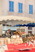 Cheese and hams overflowing market stall, Llle-Rousse, Corsica, France