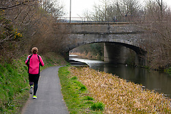 Edinburgh, Scotland, UK. 25 March, 2020. Day two of the Government enforced lockdown in the UK. All shops and restaurants and most workplaces remain closed. Cities are very quiet with vast majority of population staying indoors. Pictured; A jogger taking her daily exercise alongside the Union Canal at Hermiston in Edinburgh. Iain Masterton/Alamy Live News