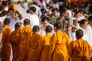 20 OCTOBER 2012 - BANGKOK, THAILAND: Buddhist monks walk through a crowd of people in a Bangkok park accepting alms for monks in southern Thailand who can't leave their temples because of anti-Buddhist religious violence. More than 2,600 Buddhist Monks from across Bangkok and thousands of devout Thai Buddhists attended the mass alms giving ceremony in Benjasiri Park in Bangkok Saturday morning. The ceremony was to raise food and cash donations for Buddhist temples in Thailand's violence plagued southern provinces. Because of an ongoing long running insurgency by Muslim separatists many Buddhist monks in Pattani, Narathiwat and Yala, Thailand's three Muslim majority provinces, can't leave their temples without military escorts. Monks have been targeted by Muslim extremists because, in the view of the extremists, they represent the Thai state.        PHOTO BY JACK KURTZ