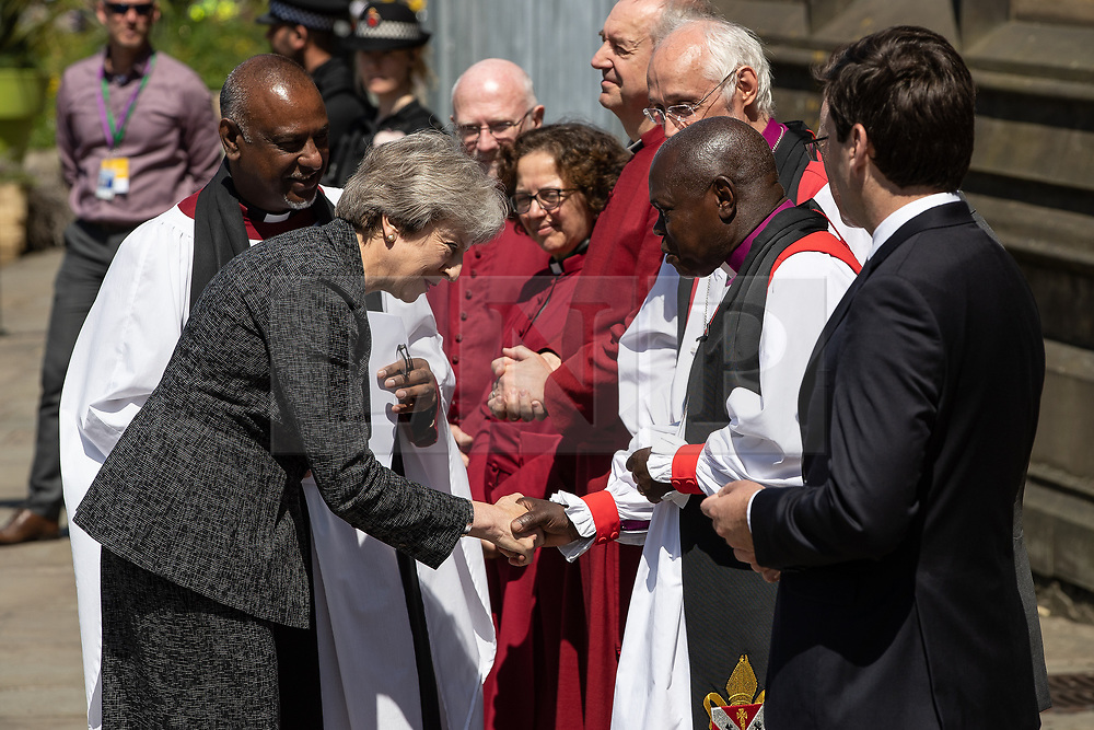© Licensed to London News Pictures . 22/05/2018 . Manchester , UK . Prime Minister THERESA MAY is greeted by dignitaries , including Bishop DAVID WALKER  JOHN SENTAMU (shaking hands), SIR RICHARD LEESE and ANDY BURNHAM , wait to receive guests at Manchester Cathedral ahead of a Service of Remembrance on the first anniversary of the Manchester Arena bombing . On the evening of 22nd May 2017 , Salman Abedi murdered 22 people and seriously injured dozens more , when he exploded a bomb in the  foyer of the Manchester Arena as concert-goers were leaving an Ariana Grande gig . Photo credit : Joel Goodman/LNP