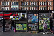 An elderly lady struggles with her shopping trolley past a graffiti-covered bus stop in Brixton, on 30th january 2019, in Lambeth, south London, England.