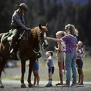A ranger on horseback talking to tourists in Yellowstone National Park.