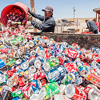 062613       Cable Hoover<br /> <br /> Employee Jacob Harrison empties a barrel full of aluminum cans into a bin at All City Recycling in Gallup Wednesday.