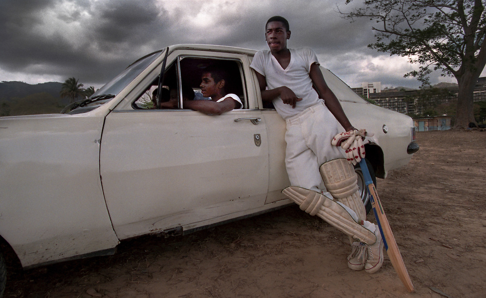 A young lad watches from the sidelines with friends while waiting to bat during the High School Cricket Championships in Port of Spain, Trinidad. (1995)