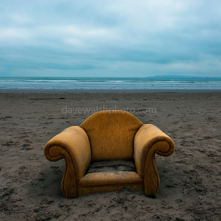 """Armchair washed up on Dollymount Strand, Bull Island, Dublin, February 2009. While this image is instantly symbolic of out throwaway Western culture, it also speaks of how some of us in the west have lapsed into the luxurious idea that we're doing enough to save the environment. We  might eat less meat, drive less, take less flights, recycle, vote Green, and change our lightbulbs, but as we sit smugly in our middle class armchairs, we should realise that despite our actions, sea levels are rising, and a """"trash vortex"""" is now forming in the Atlantic Ocean. Are we really doing enough?This image is from an ongoing, long term photography project, on the use AND misuse of Bull Island, a 200 year old island, sandback and UNESCO Biosphere at the north end of Dublin Bay, Ireland. This collection plans to cover the wildlife - both human and other, and challenge the misuse of an elaborate ecosystem on the edge of Dublin city."""