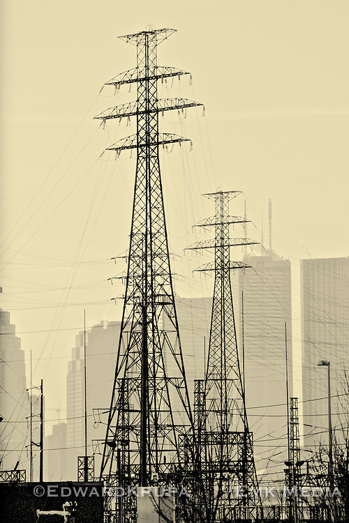 Electricity pylons, or transmission towers, loom over city at sunset. Toronto, Ontario, Canada.