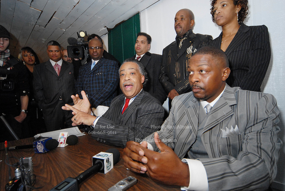 Rev. Sharpton gestures as he amswers questions from the media at a brief press conference after his remarks at the Antioch Baptist Church. Sharpton commented on the planned Nationalist rally on MLK day in Jena on Monday.The town of Jena Louisiana rescheduled their Martin Luther King Holiday festivities from Monday to Sunday because the Nationalist Movement planned a march in Jena on MLK day. Sharpton came to Jena the day before Martin Luther King holiday because the Nationalist Movement lead by Richard Barrett is to march on Jena Monday during MLK holiday. The Nationalist movement is coming to Jena in response to the Jena 6 rally last year. Sharpton was in Jena to protest the Jim Crow Justice still prevalent in the south. Sharpton discussed his feeling about MLK's legacy and how it should be celebrated and that their are still, today in the South many things to fight for, Equal Justice would be at the top of his list. Sharpton said you can not heal the community until justice is dealt with fairly, no white justice or black  justice -Equal Justice for all is what will heal the town of Jena.Seated next to Sharpton is Marcus Jones, Mychael Bell's father, standing behind Sharpton is John Jenkins, Carwin Jones's father,black suit. Carwin and Bell are part of the Jena 6.(Photo/© Suzi Altman)