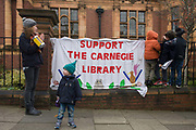 Children and a home-made banner asking for local support for Lambeth's public libraries. Faced with the closure of its beloved local library, the people of Herne Hill, Lambeth, south London hold a demonstration outside the Edwardian property. Lambeth council plan to close the facility used by the community as part of austerity cuts, saying they will convert the building into a gym and privately-owned gentrified businesses - rather than a much-loved reading and learning resource. £12,600 was donated by the American philanthropist Andrew Carnegie to help build the library which opened in 1906. It is a fine example of Edwardian civic architecture, built with red Flettan bricks and terracotta, listed as Grade II in 1981.