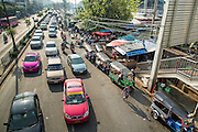 """26 SEPTEMBER 2012 - BANGKOK, THAILAND: Traffic on Rama IV Road in front of Khlong Toey Market in Bangkok. Khlong Toey (also called Khlong Toei) Market is one of the largest """"wet markets"""" in Thailand. The market is located in the midst of one of Bangkok's largest slum areas and close to the city's original deep water port. Thousands of people live in the neighboring slum area. Thousands more shop in the sprawling market for fresh fruits and vegetables as well meat, fish and poultry.     PHOTO BY JACK KURTZ"""
