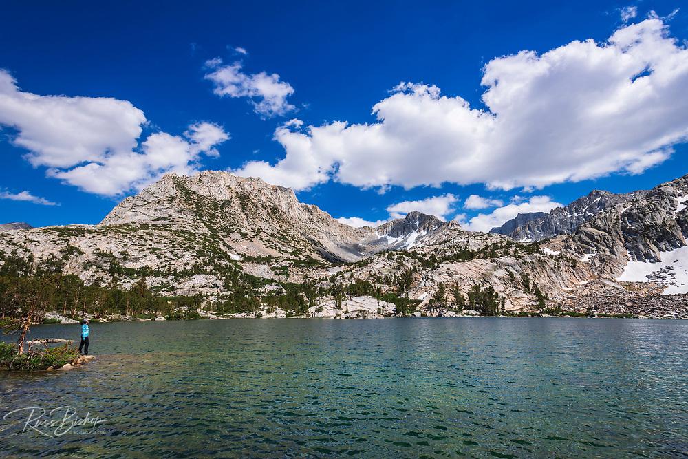Hiker on the shore of Treasure Lake under the Sierra Crest, John Muir Wilderness, Sierra Nevada Mountains, California USA