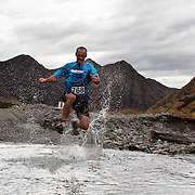 Runner Owen Hab crosses  Moke Creek on the Ben Lomond High Country Station during the Pure South Shotover Moonlight Mountain Marathon and trail runs. Moke Lake, Queenstown, New Zealand. 4th February 2012. Photo Tim Clayton