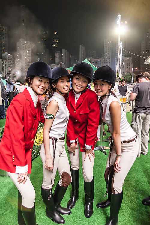 Happy Valley Racecourse girls in Hong Kong, China.   Attending a thrilling horse race meeting gets your senses awake and adrenaline flow.  The excitement under the lights of the Happy Valley Racecourse is something you don't forget. It is an opportunity to capture the essence and the vitality of Hong Kong Chinese sports culture.