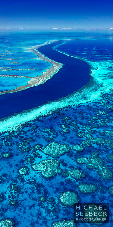 Beautiful patterns of blue and aqua feature in this vertical format photograph of a channel coursing through a section of the Great Barrier Reef.<br /> <br /> Limited Edition of 125