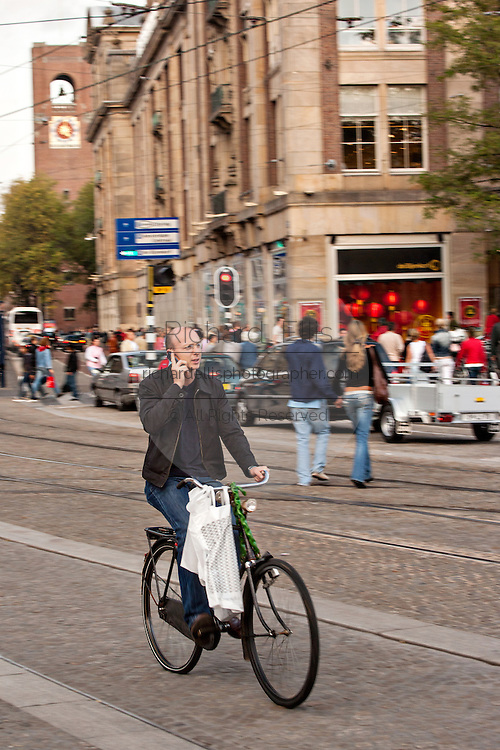 Bicyclist speaks on a mobile phone Prins Hendrikkade in Amsterdam.