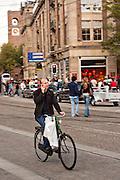Bicyclist speaks on a mobile phone Prins Hendrikkade in Amsterdam.