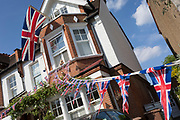 As the Coronavirus lockdown continues over the May Bank Holiday, the nation commemorates the 75th anniversary of VE Day (Victory in Europe Day, the day that Germany officially surrendered in 1945) and in Dulwich, neighbours and residents emerge from their homes to party while still observing social distancing rules. A house has a large Union Jack and bunting hanging from a window, on 8th May 2020, in London, England.