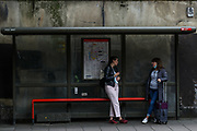 London, United Kingdom, July 10, 2021: Two passengers carrying a face protective surgical mask to curb the spread of coronavirus are seen talking at a public transport bus stop in London on Saturday, July 10, 2021. The UK reported 34 deaths and 32,367 new cases on Saturday. Over the past week, cases have grown by 30% in the United Kingdom. (VX Photo/ Vudi Xhymshiti)