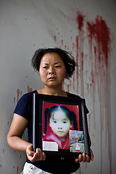 Wu Xianfang, 35, holding a picture of her daughter Wei Yu, 10, is seen at Fuxin No.2 Primary  School in Wufu, Sichuan province.