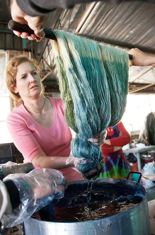 A workshop member tests a skein of mohair yarn in the indigo vat. It has been pre-mordanted to a soft yellow. Indigo dye and bogolan workshop held with Aboubakar Fofana in Johannesburg, South Africa