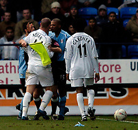 Photo. Jed Wee.<br /> Bolton Wanderers v Fulham, FA Cup 5th Round, 19/02/2005.<br /> Fulham's Collins John (R) has to be held away from Bolton's Kevin Nolan by the referee's assistant as tempers flare.