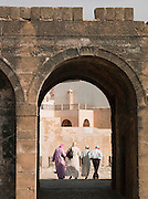 People walk along the ramparts of the old fortified wall at Essaouira medina in Morocco