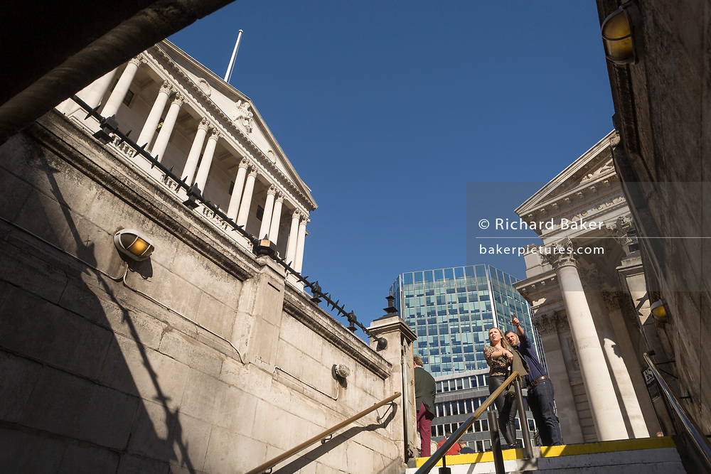A man points directions at the top of steps of Bank Underground station, beneath the Bank of England and neo-classical pillars of Royal Exchange in the City of London - the capital's financial centre (aka The Square Mile), on 27th September 2018, in London, England.