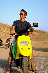 handsome man sitting on a moped in Greece