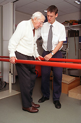 Young male physiotherapist working with elderly man helping him to walk using parallel bars,