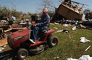 Rainsville, Alabama: Harold Parris, who survived being flung out of his storm cellar by the tornados, tests out his wrecked lawn mower in front of his wrecked trailer home. At least 33 people are confirmed dead in Rainsville and surrounding DeKalb County in northeastern Alabama. (PHOTO: MIGUEL JUAREZ LUGO)