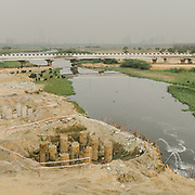 The Barapullah sewer drainage, as it exits directly into the Yamuna. Construction site as well. <br /> Authorities have proclaimed the drainage waters too dirty to wash animals in it - yet buffaloes wash in it. Their milk is collected for human consumption.