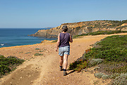 One woman walking the cliff top coastal long distance footpath trail, The Fisherman's Trail or Ruta Vicentina, near Zambujeira do Mar, Alentejo Littoral, Portugal, Southern Europe