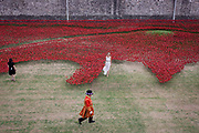 Marking the centenary of the beginning of the First World War (WW1) in 1914, a Tower of London Beefeater walks past TV presenters among some of the 888,246 ceramic poppies - one for each British military death - created by artist Paul Cummins. Remaining in place until the date of the armistice on November 11th. Across the world, remembrance ceremonies for this historic conflict that affected world nations, London saw many such gestures to remember the millions killed in action at the beginning of the 20th century.