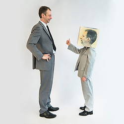 Boy wearing mask and showing thumbs up to businessman