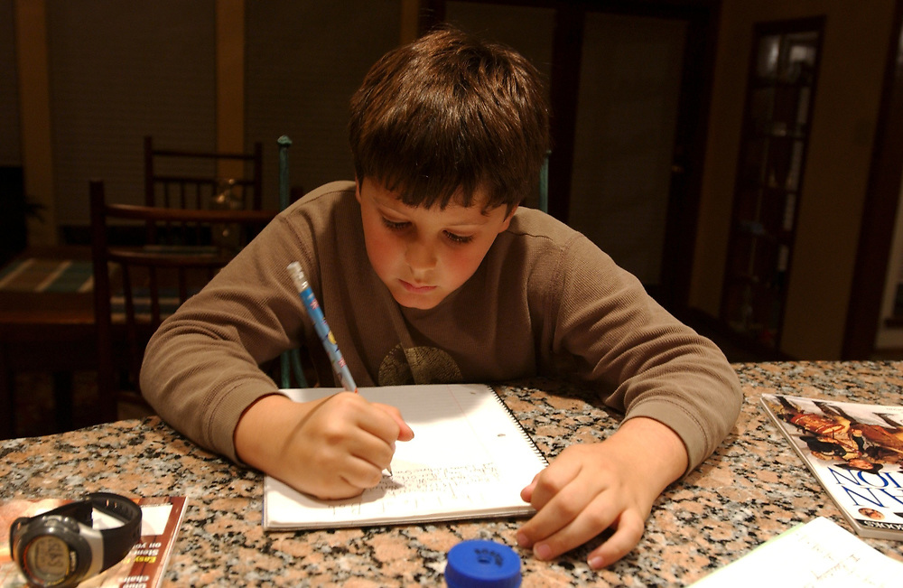 Nine-and-a-half year old Anglo boy 4th grader completes ahomework assignment  MR ©Bob Daemmrich