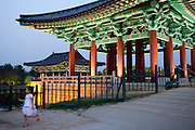 """Girl during an evening at Anapji pond in the city of Gyeongju. Gyeongju was the capital of the ancient kingdom of Silla (57 BC - 935 AD) which ruled most of the Korean Peninsula between the 7th and 9th centuries. A vast number of archaeological sites and cultural properties from this period remain in the city. Gyeongju is often referred to as """"the museum without walls"""". / Gyeongju, South Korea, Republic of Korea, KOR, 20th of May 2010."""
