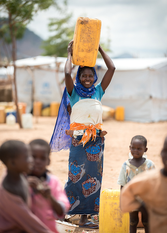 30 May 2019, Mokolo, Cameroon: A woman prepares to carry a jerry can home from one of the distribution points for drinking water in Minawao. The Minawao camp for Nigerian refugees, located in the Far North region of Cameroon, hosts some 58,000 refugees from North East Nigeria. The refugees are supported by the Lutheran World Federation, together with a range of partners.