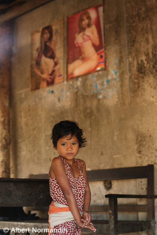 Young girl with sexy woman posters in background in old abandoned building, Thandwe